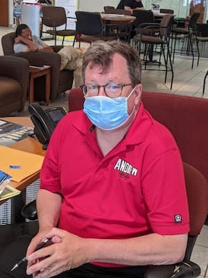 man sitting in chair with face mask