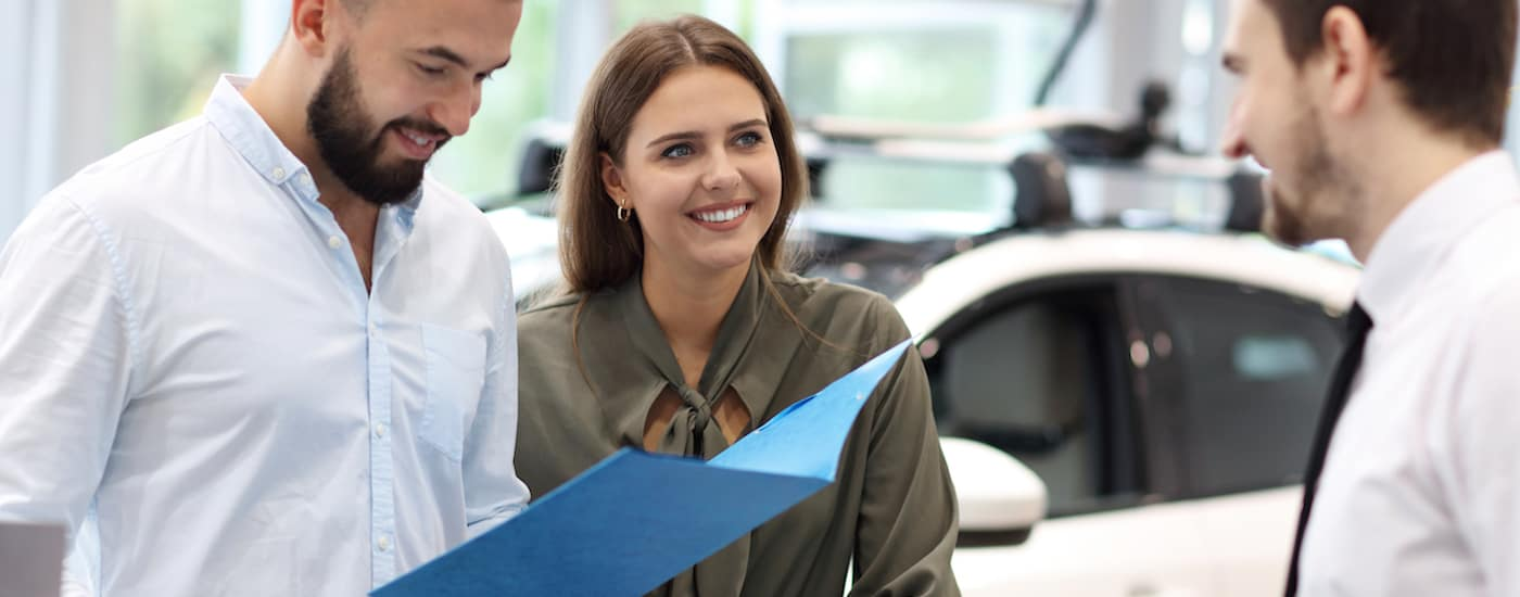 A couple with a blue folder is talking to a salesman.