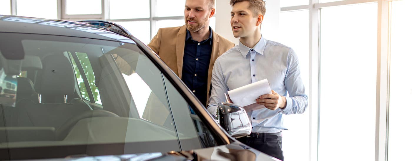 A man and salesman are looking at a car in a showroom.