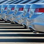 A close up of the rear bumpers on a line of sedans is shown at a buy here pay here car lot.