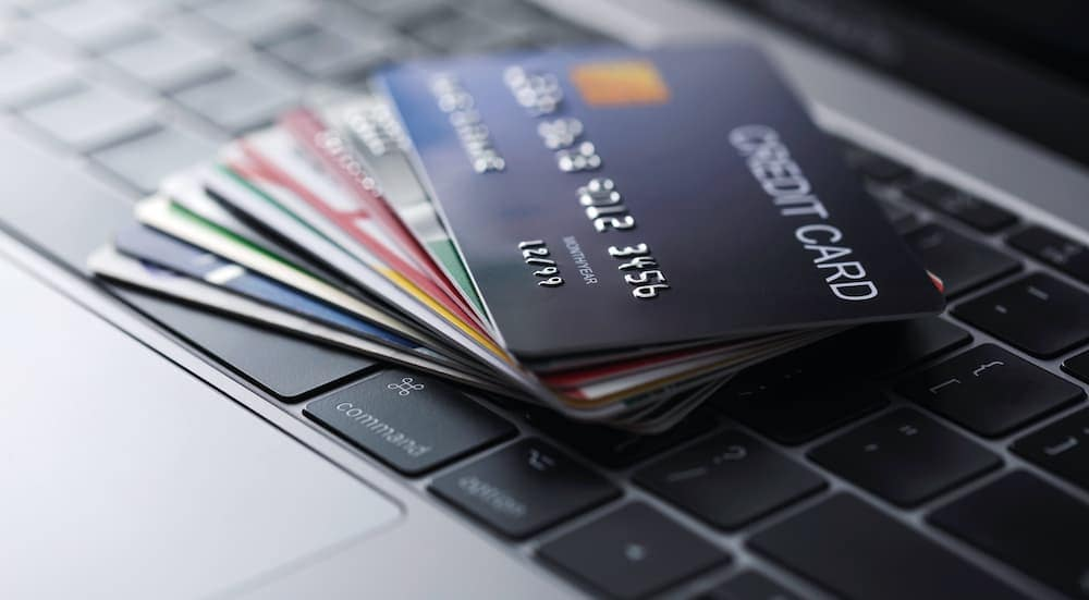 A stack of fanned out credit cards is sitting on a laptop keyboard.