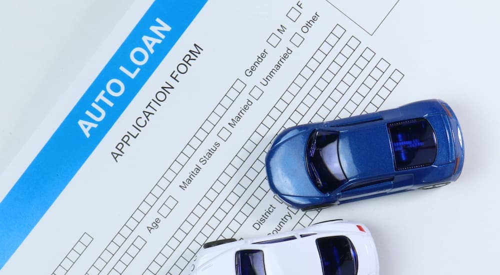 A close up is shown of a blue and a white toy car on top of a car loan application at a bad credit car lot in Kansas city.