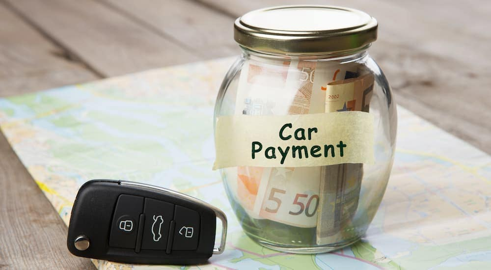 A close up is shown on a car payment jar and set of car keys.