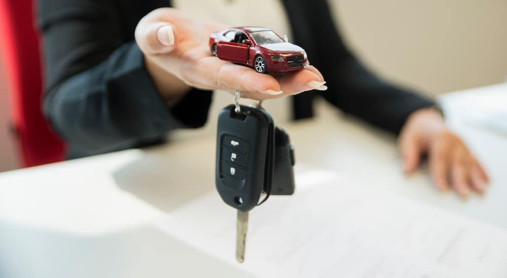A close up is shown of a hand holding out a die-cast car and set of car keys.