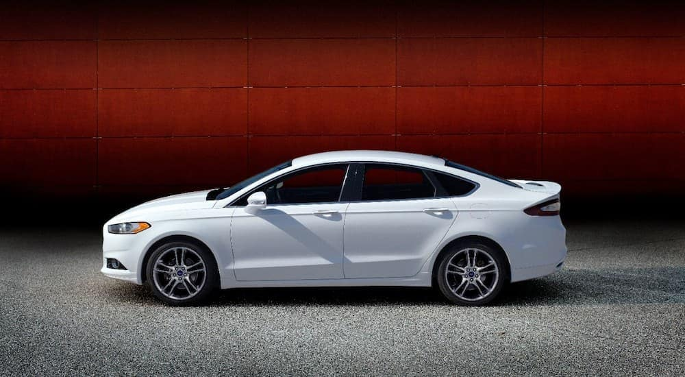 A white 2013 Ford Fusion is shown from the side, parked on the asphalt in front of a red wall.