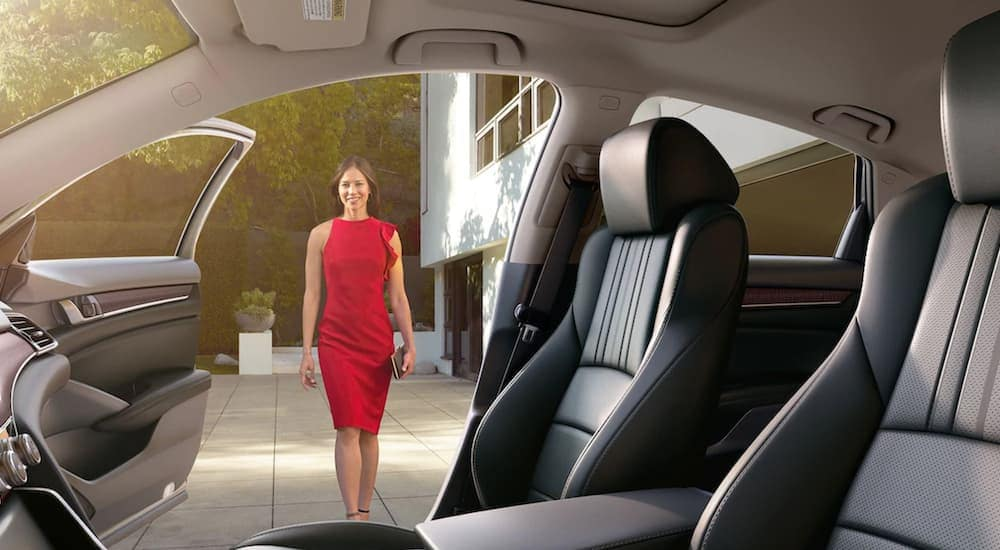 A woman in a red dress is shown approaching the open passenger door of a 2020 Honda Accord.