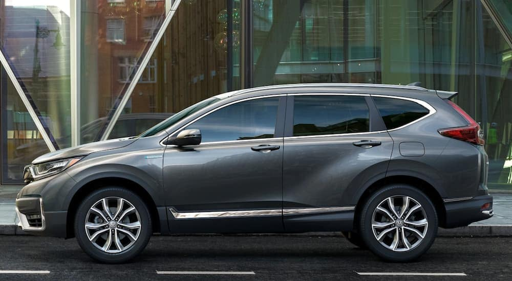 A dark grey 2020 Honda CR-V Hybrid is shown from the side with a glass building in the background, after leaving a Buy Here Pay Here in Kansas City.