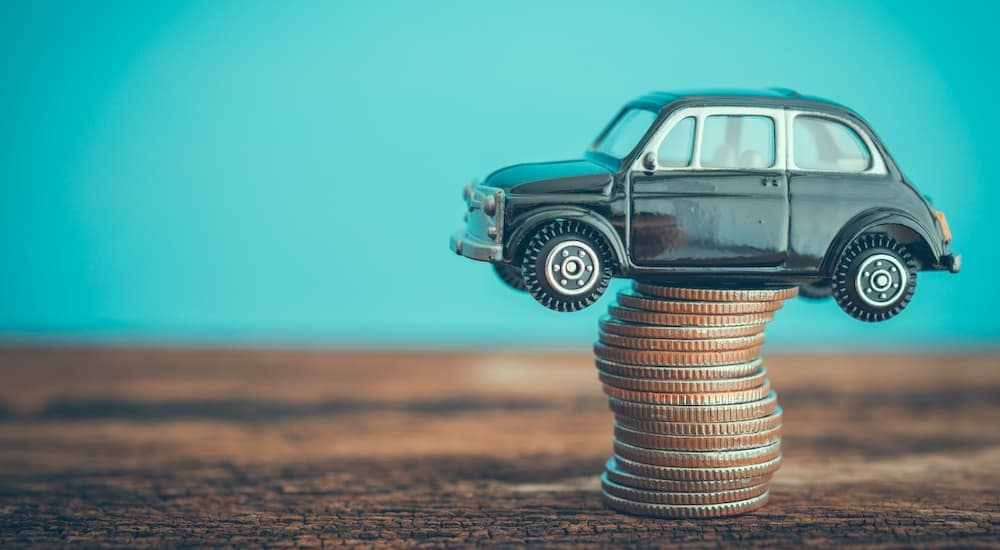 A toy car is shown perched on top of a stack of quarters.