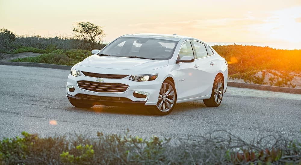 A white 2016 Chevy Malibu is shown from the front, parked in an empty lot with the sun setting in the background.
