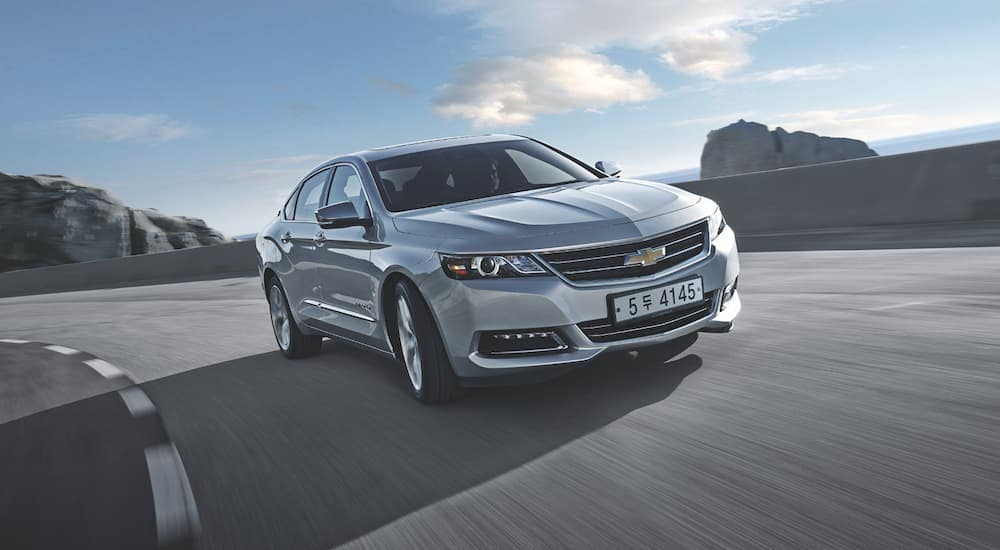 A silver 2016 Chevy Impala is rounding a corner after leaving a popular buy here pay here car loan dealer.