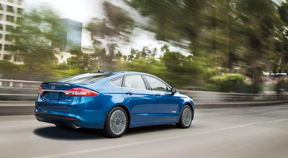 A blue 2017 Ford Fusion is speeding past blurred trees and buildings.