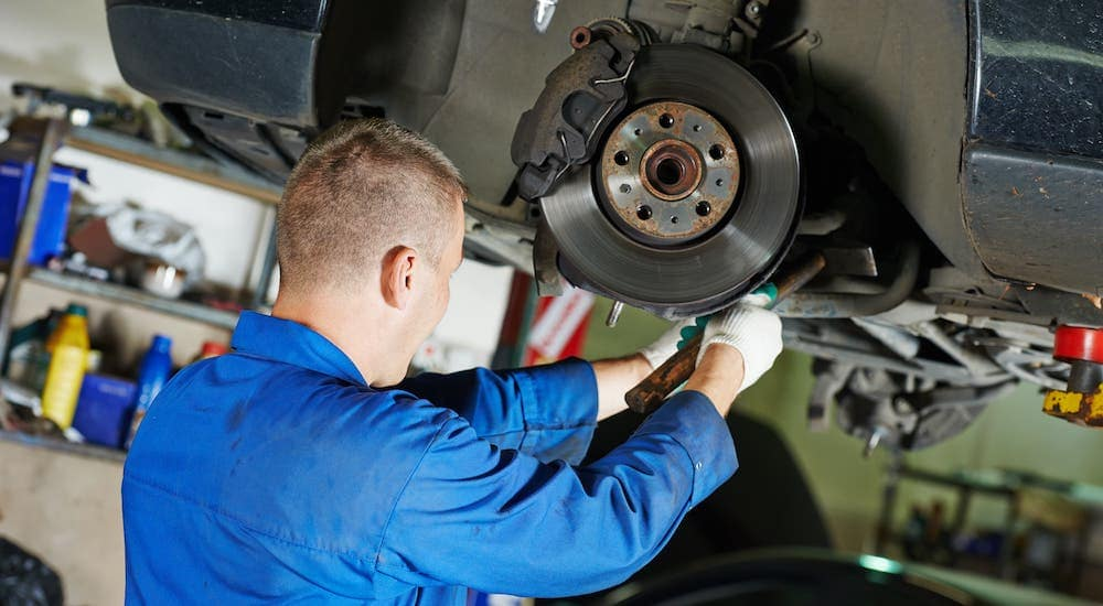 A mechanic is shown working on the breaks of a car on a lift.