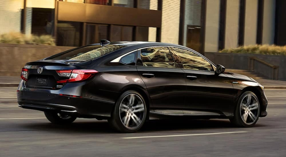 A 2021 crystal black pearl Honda Accord Hybrid shown from the side is driving through an urban area.