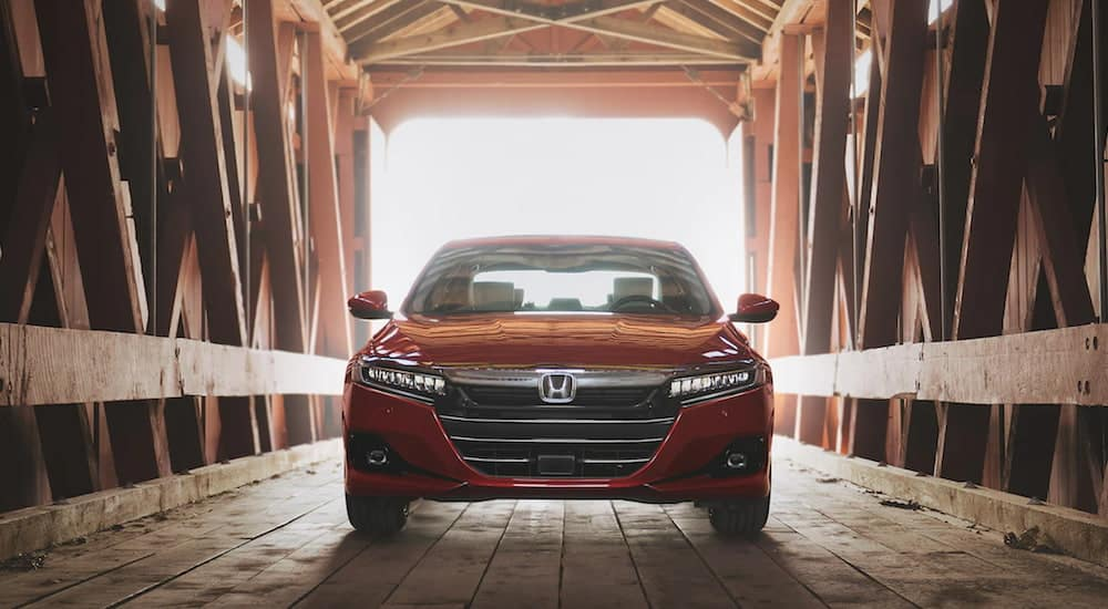 A radiant red metallic 2021 Honda Accord Touring 2.0T is driving through a covered bridge after leaving a buy here, pay here in Olathe, KS.