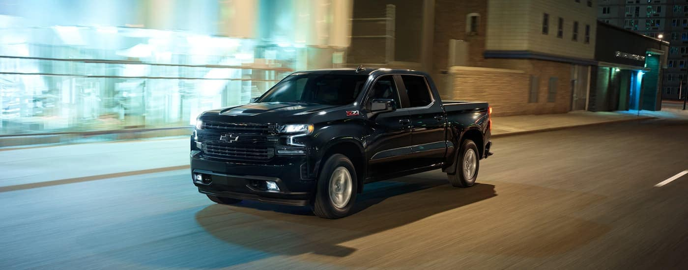 A black 2021 Chevy Silverado Z71 is shown from the side driving through the city after the 2021 Chevy Silverado vs 2021 Ford F-150 comparison.