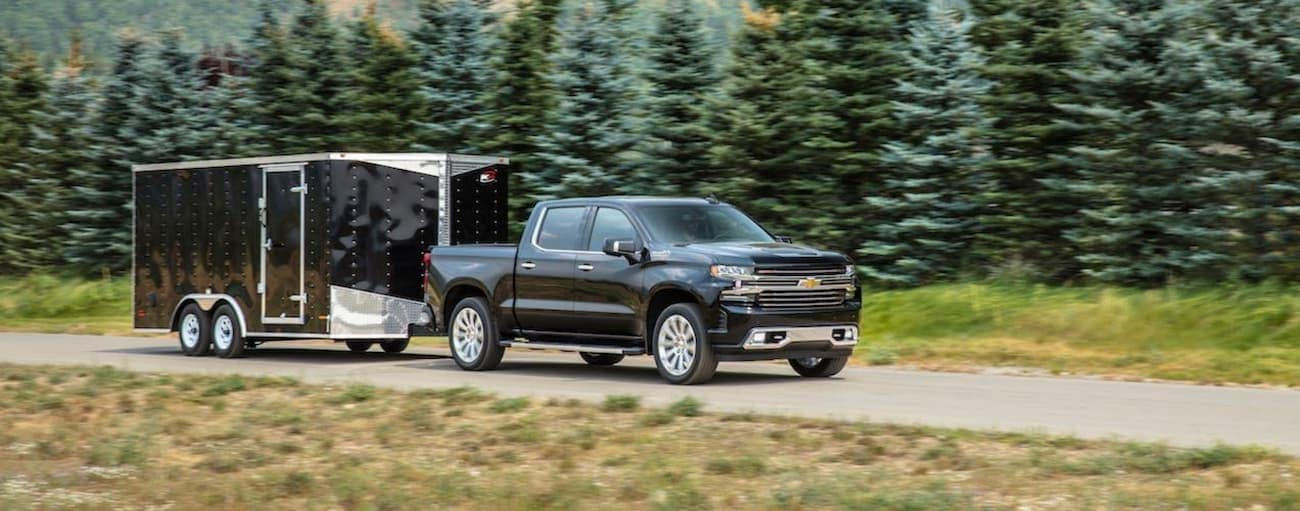A black 2020 Chevy Silverado 1500 is towing a black enclosed trailer past pine trees.