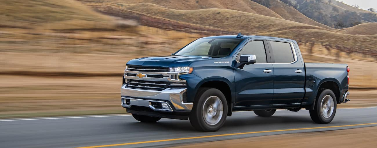 A blue 2020 Chevy Silverado 1500 is driving past blurred hills outside Indianapolis, IN.