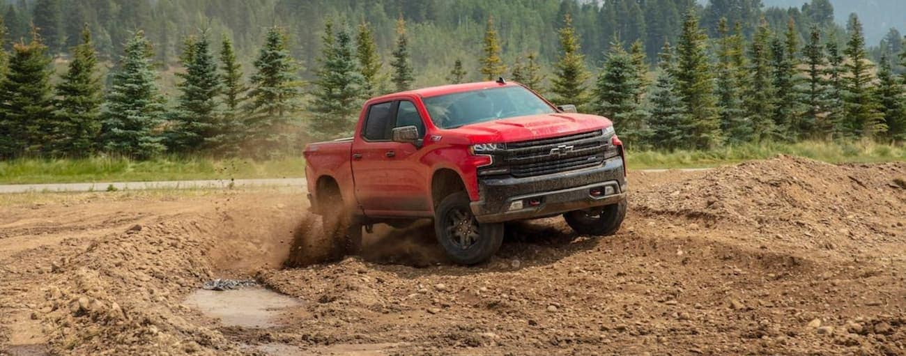 A red 2020 Chevy Silverado 1500 is off-roading in the mud.