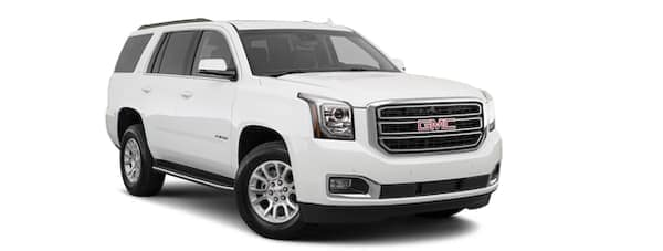 A white 2019 GMC Yukon is facing right.