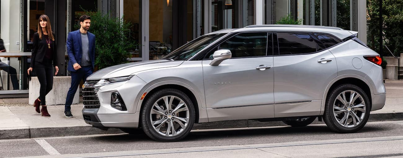 A couple is walking toward a silver 2020 Chevy Blazer parked on a city street.