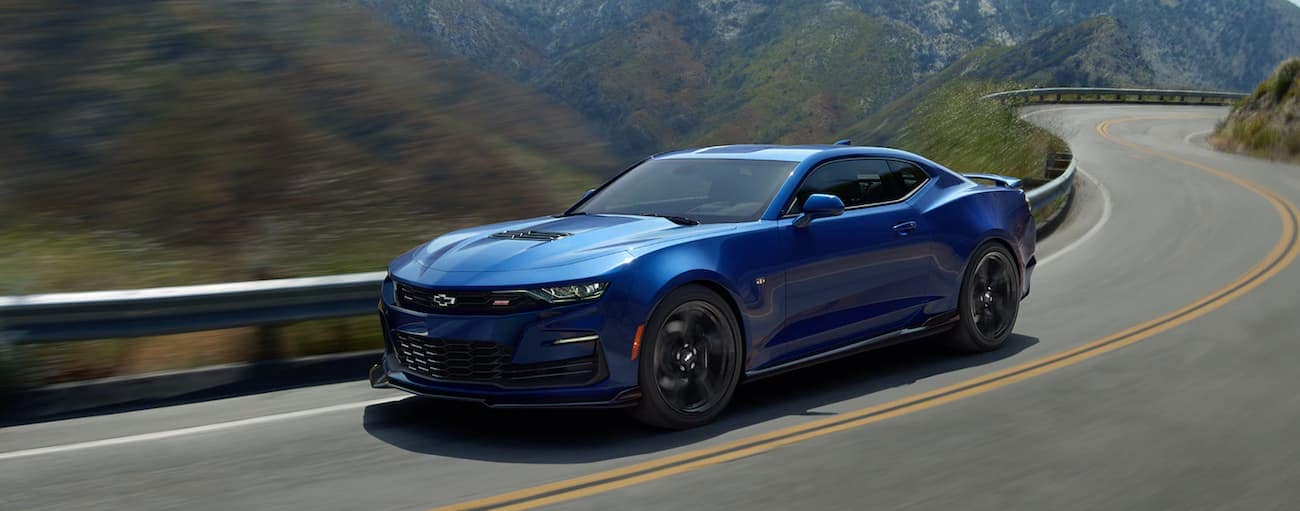 A blue 2020 Chevy Camaro is driving on a winding road through hills.