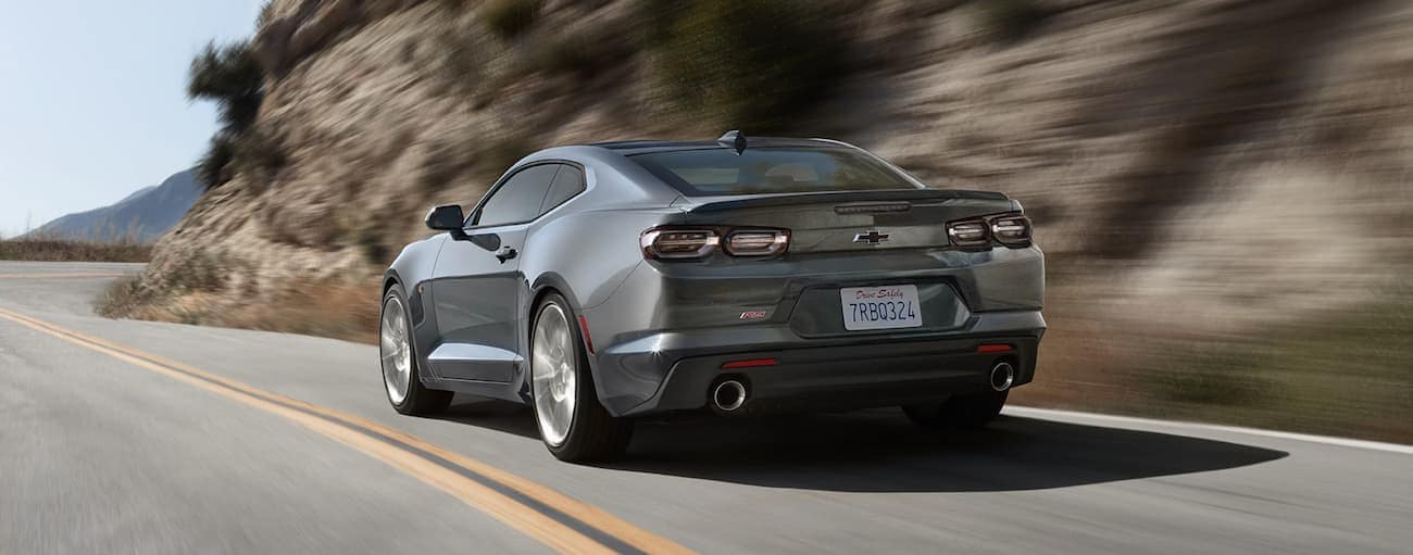 A grey 2020 Chevy Camaro is driving on a road lined with rock face.