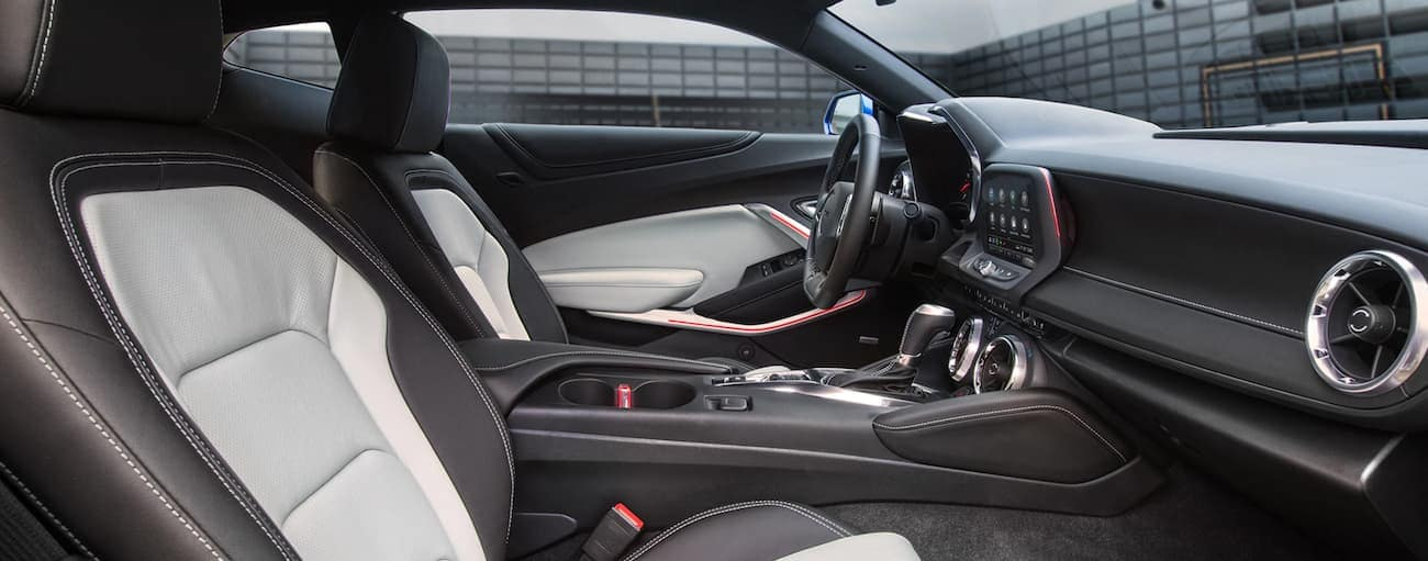 The white and black interior of a 2020 Chevy Camaro is shown with an Indianapolis building outside.