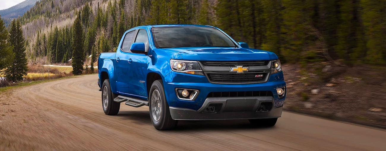 A blue 2020 Chevy Colorado Z71 is driving on a dirt road in front of a mountain.