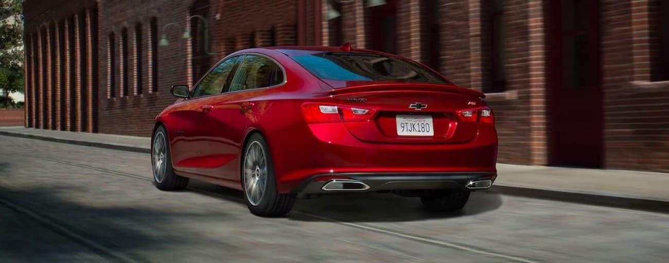 A red 2020 Chevy Malibu RS is driving away on an Indianapolis street past a brick building.