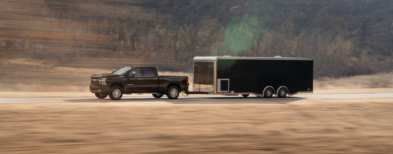 A black 2020 Chevy Silverado 2500 High Country is towing a black enclosed trailer on a highway outside Indianapolis, IN.
