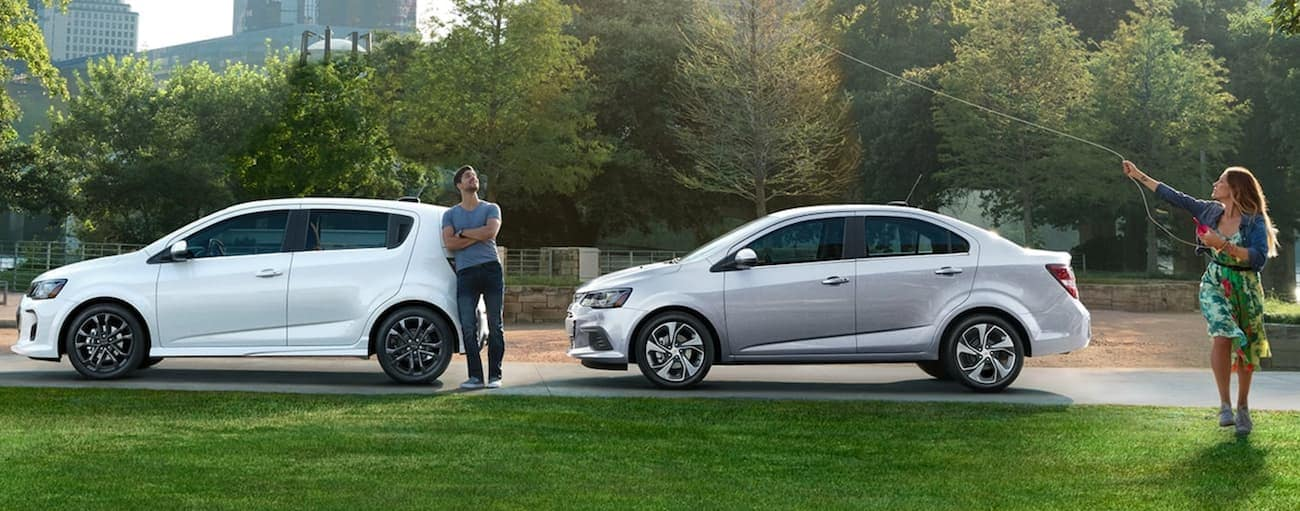 A man is standing next to a white 2020 Chevy Sonic Hatchback, while a woman flies a kite next to a silver Sonic sedan.