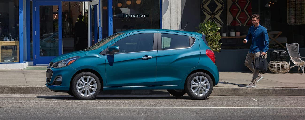 A man is walking toward a blue 2020 Chevy Spark parked on a city street in Indianapolis, IN.