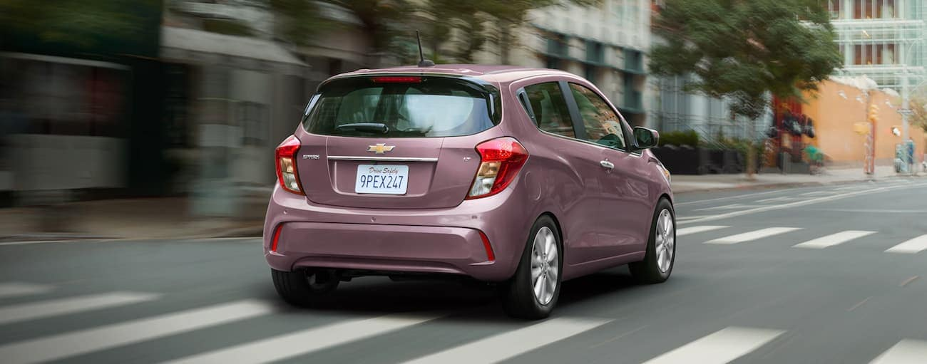 A pink 2020 Chevy Spark is driving away on a city street.