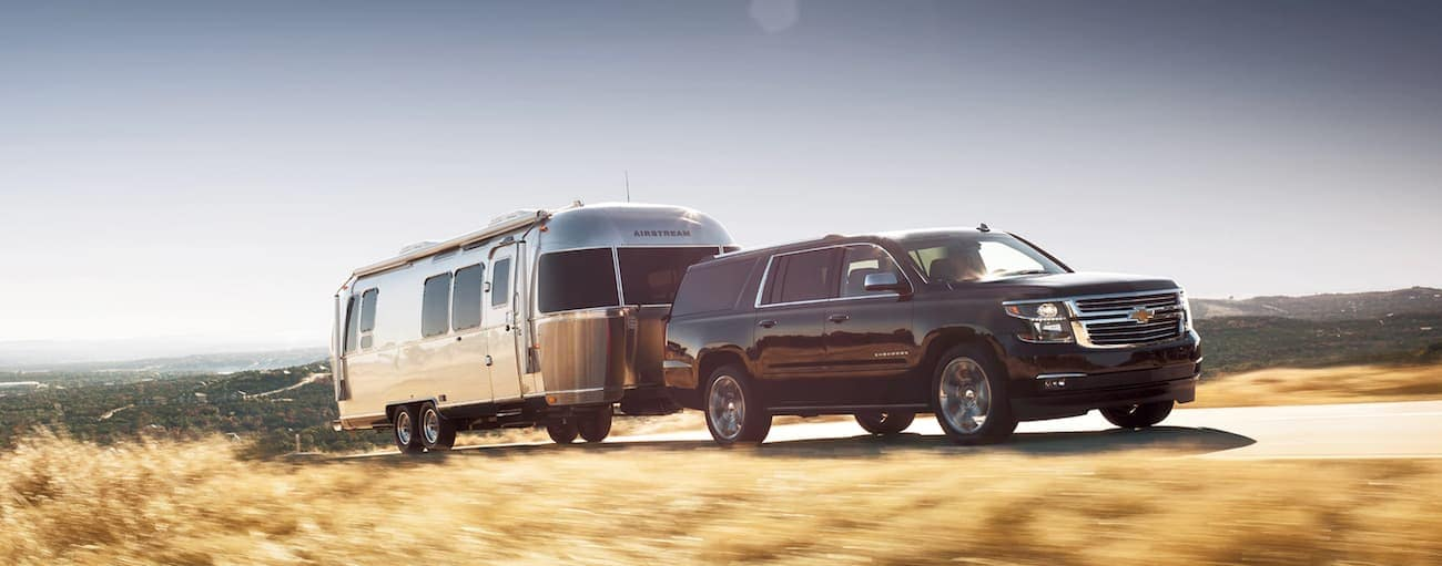 A black 2020 Chevy Suburban is towing an Airstream past yellow grass.