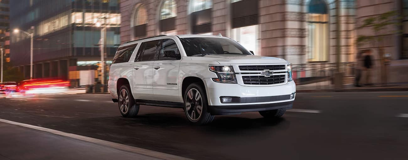 A white 2020 Chevy Suburban is driving down a street in Indianapolis, IN, at night.