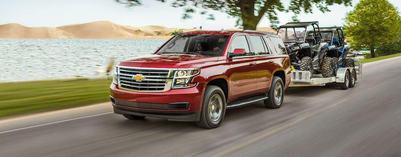 A red 2020 Chevy Tahoe is towing side-by-sides past a lake.
