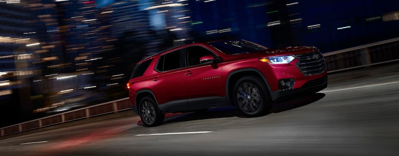 A red 2020 Chevy Traverse RS is driving on a city street at night.