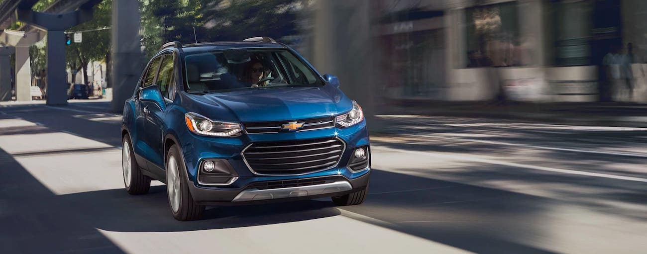 A blue 2020 Chevy Trax is driving under an overpass.