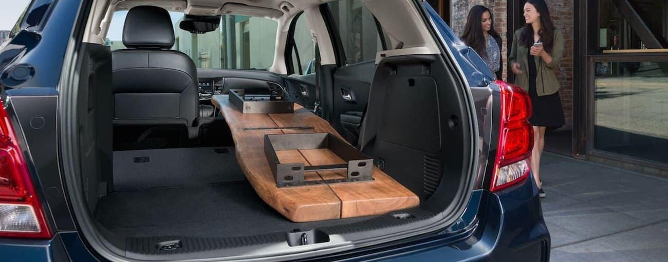 A wood table is in the cargo space of a 2020 Chevy Trax parked on an Indianapolis, IN street.