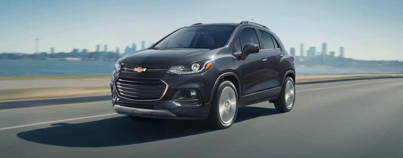 A grey 2020 Chevy Trax is driving away from a city skyline.