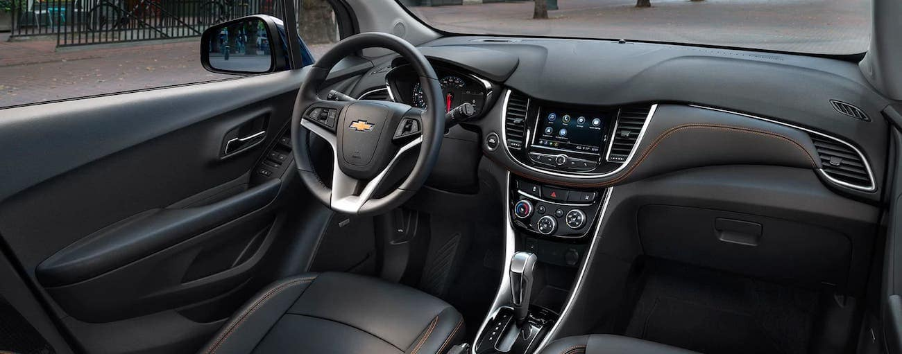 The black interior with orange stitching is shown in a 2020 Chevy Trax.