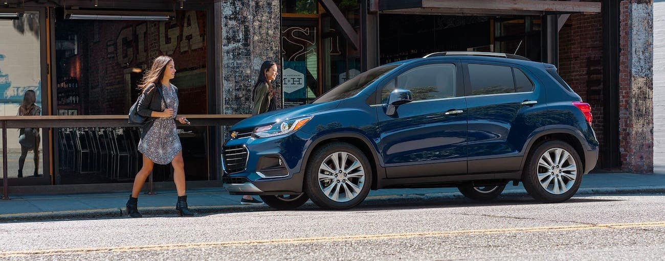 Two women are walking towards a blue 2020 Chevy Trax which is parked on an Indianapolis street.