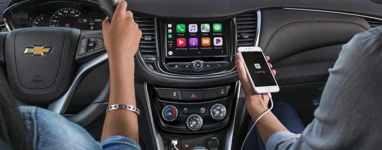 A driver and passenger are using the infotainment features with a phone connected to a 2020 Chevy Trax.