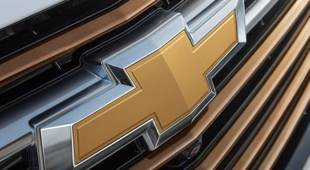 A closeup is shown of the yellow Chevrolet badge on a white 2021 Chevy Equinox.