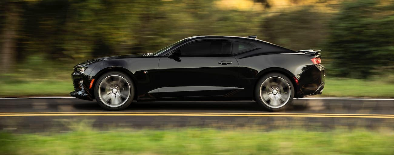 A black 2016 used Chevrolet Camaro is shown driving from the side on a tree-lined road.