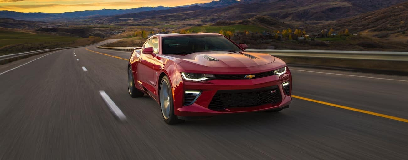 A red 2017 used Chevrolet Camaro is driving on a highway at sunset with mountains in the distance.