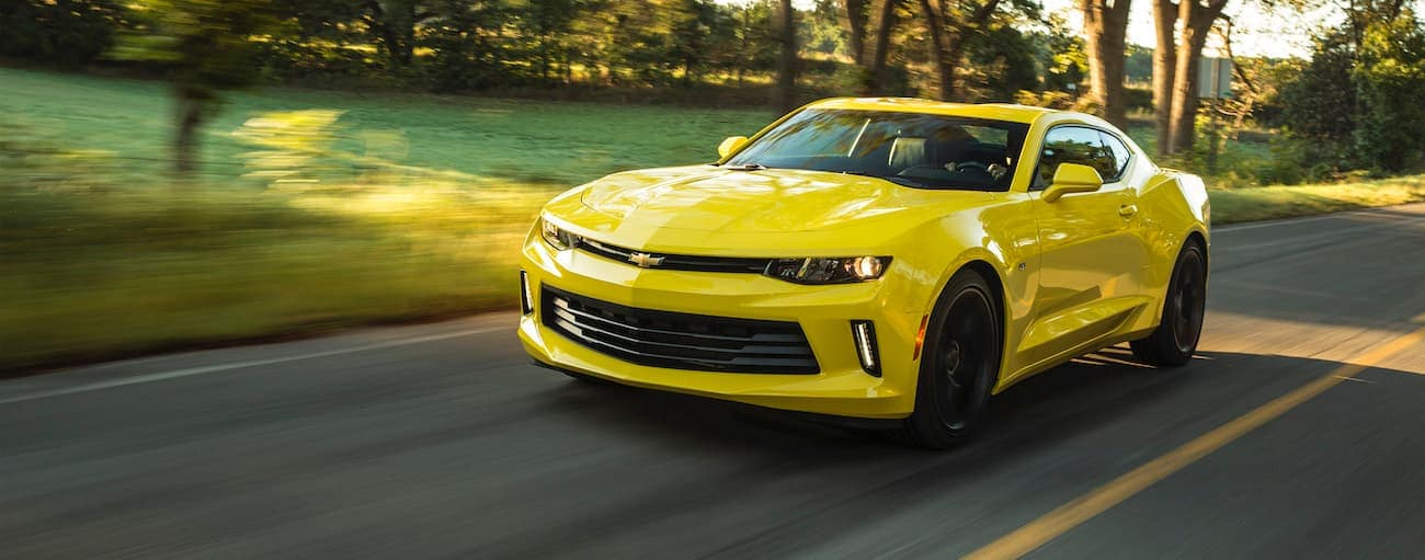 A yellow 2018 used Chevrolet Camaro is driving on a sunny road outside of Indianapolis, IN.