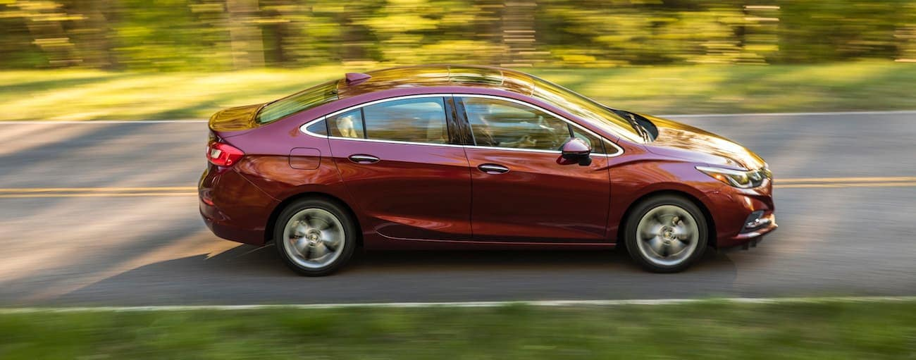 A red 2016 used Chevrolet Cruze is shown driving from the side on a sunny road.