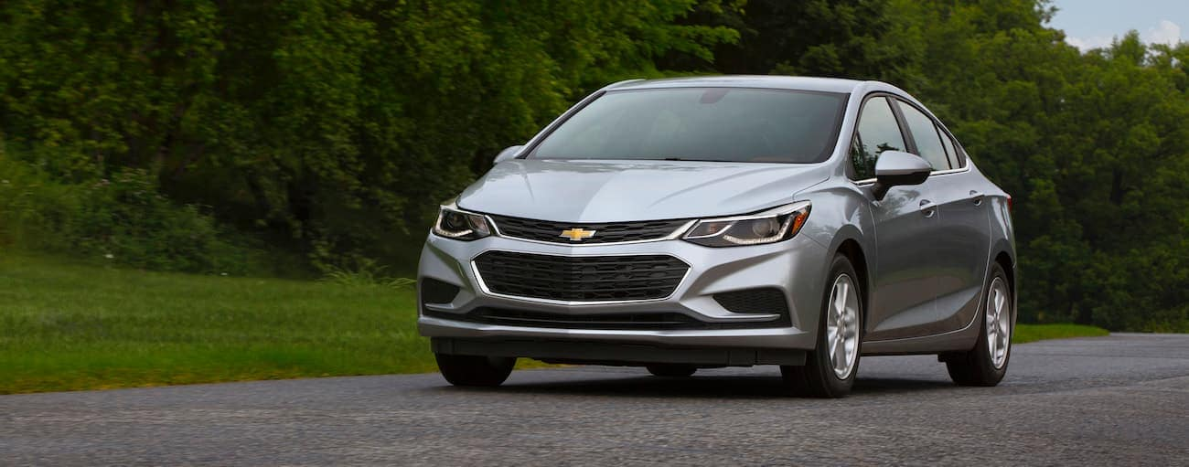 A silver 2017 used Chevrolet Cruze is driving on a tree-lined road near Indianapolis, IN.