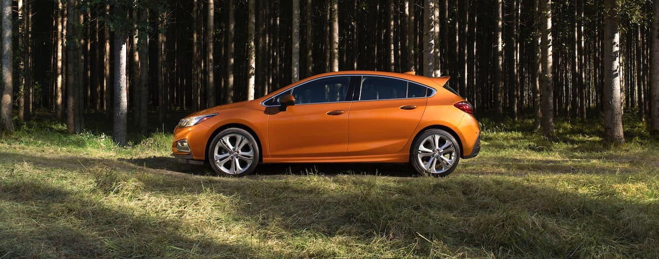 An orange 2018 used Chevrolet Cruze is shown from the side on a trail in the woods.